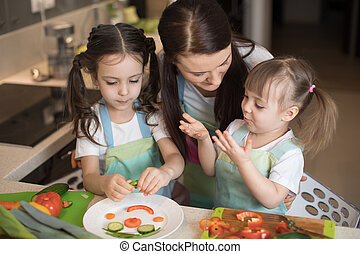 happy family mother and her kids are preparing healthy food, they improvise together in the kitchen