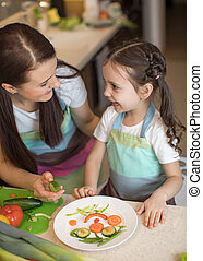 happy family mother and kid girl are preparing healthy food, they improvise together in the kitchen