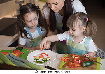 happy family mother and kids are preparing healthy food, they improvise together in the kitchen