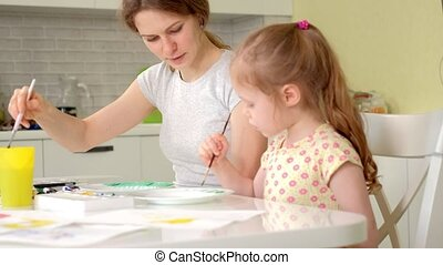Happy family, mother and little daughter paint with paint on white plates