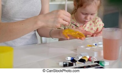 Happy family, mother and little daughter paint with palms on their palms