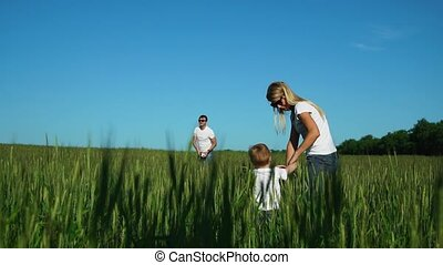 Happy family: mother and son go to the field to his father who plays with a football