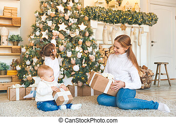 happy family mother and two children on Christmas morning tree with gifts