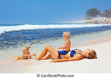 Happy family - mother, baby son, daughter sunbathing on sea beach