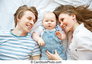 Happy family mother father and baby in bed