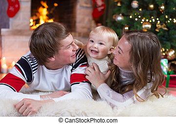 Happy family - mother, father and baby little boy playing in the winter for the Christmas holidays