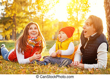 happy family mother father and baby on autumn walk in park