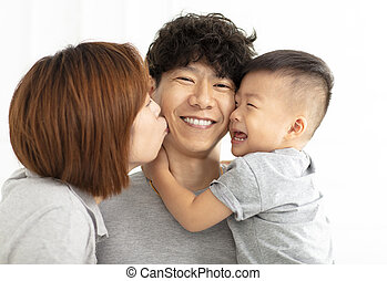 happy family mother, father and child kissing