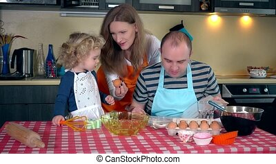 happy family mother father and cute daughter making cookie together in kitchen
