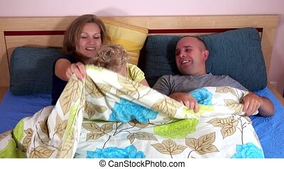 Happy family mother father and toddler girl have fun under...