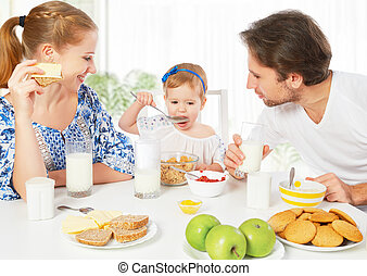Happy family mother, father, child baby daughter having breakfas