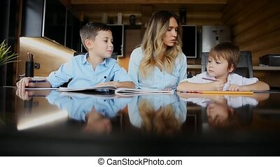 Happy family mother of two children helps the sons to do their homework sitting at the big table in the kitchen.