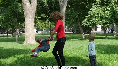 Happy Family: mother rotating twisting making circle with her little daughters. Slow motion
