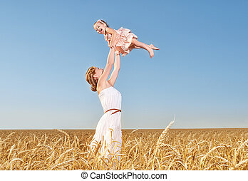 happy family mother throws the baby into the sky in summer