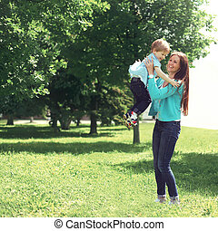 Happy family! Mother with son child is playing having fun together on the grass in sunny summer day