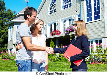 Happy family near new house. - Happy family with agent...