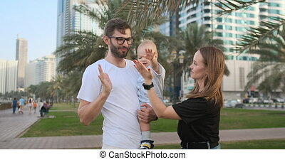 Mom father and son standing in the Park smiling and hugging looking at each other in the summer among the palm trees