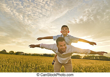 happy family of father and child on field at the sunset having fun on the father back