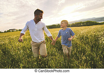 happy family of father and child on field at the sunset having fun walking on grass