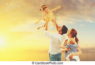 happy family of father, mother and two children, baby son and daughter on beach at sunset