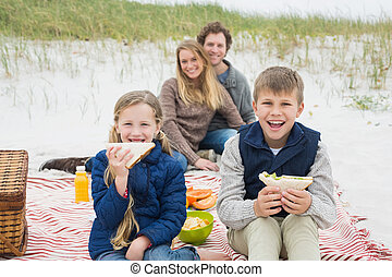 Happy family of four at a beach picnic - Portrait of a happy...
