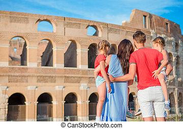 Happy family of four enjoy italian vacation on Colosseum background. Italian european family vacation in Rome