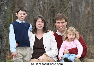 Family of four on rocks in wooded yard in winter season. (Horizontal)