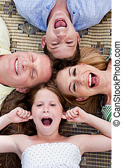 Happy family of four lying on the carpet with their heads together
