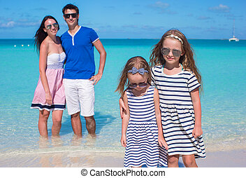 Happy family of four on beach vacation