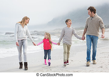 Happy family of four walking hand in hand at beach - Full...
