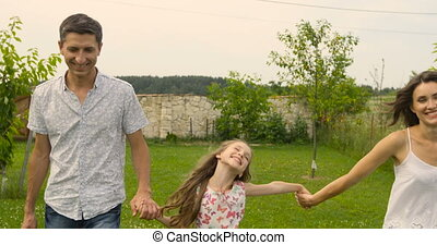Happy family of parents and daughter running holding hands on the grass in garden