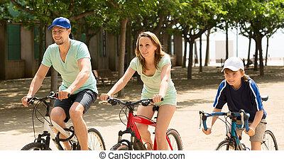 Happy family of three cycling on street