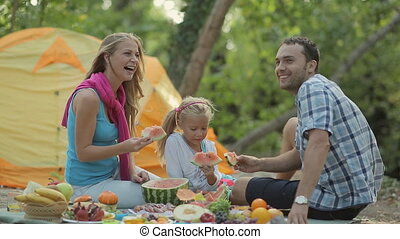 Happy family of three laughing, eating watermelon and rest on the nature