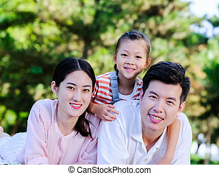 Happy family of three on the park grass