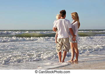 Happy Family of Three People Playing in Ocean While Walking Alon