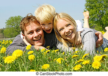 Happy Family of Three People Relaxing in Flower Meadow