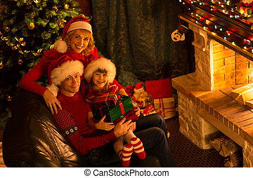 Happy family of three persons in red hats with gifts sitting at Christmas tree near fireplace