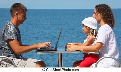 happy family of three persons sits at table with notebook, sea in background