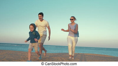 Happy family of three playing on the beach