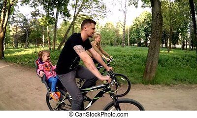 Happy Family Of Three Riding Bicycles In Green Park