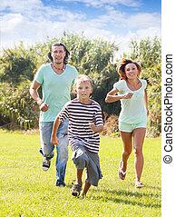 Happy family of three running on grass