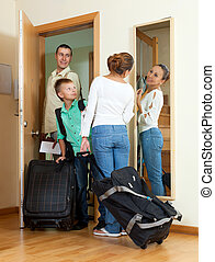 Happy family of three with teenage boy going with suitcases for vacation
