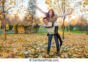 Happy family of two having fun in autumn park on a sunny fall day