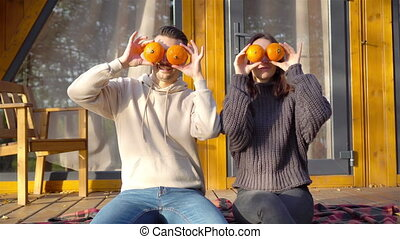 Young couple covered eyes with pumpkins at autumn warm day on the terrace of their house