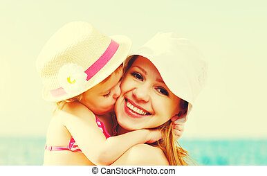 happy family on beach. baby daughter kissing mother