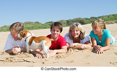 happy family on beach - a happy family lying on the beach in...