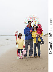 Happy family on beach with umbrella