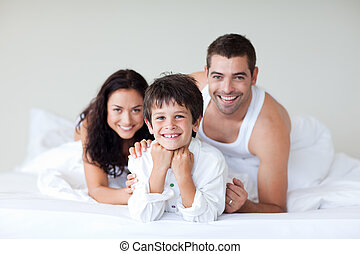 Happy family on bed with thumbs up