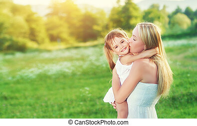 happy family on nature mother kissing little daughter