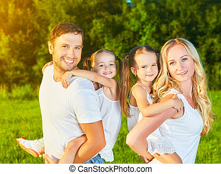 happy family on nature of summer, mother, father and children twin sisters